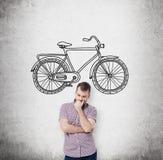 Een persoon in vrijetijdskleding denkt over betaalbare of milieuvriendelijke manieren om te reizen Een schets van fiets wordt get Stock Fotografie