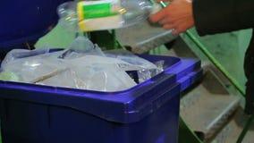 Een persoon werpt een plastic fles in het afval stock videobeelden
