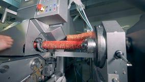 Een persoon wijst verpakking op een fabrieksmachine die toe het met vlees vult stock video