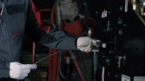 Een persoon zet een kabelsnijmachine aan en vouwt de kabel in de machine Automatische robotachtige complexe besnoeiingen de kabel stock videobeelden