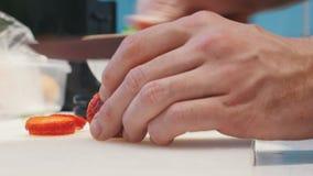 Een persoons scherpe aardbeien op plakken voor decoratie stock videobeelden