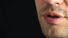 Een persoonsgefluister in de camera Close-up van de lippen gefluister op een zwarte achtergrond stock videobeelden