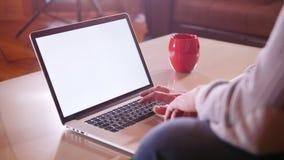 Een persoonszitting door laptop en het onttrekken op het toetsenbord stock footage