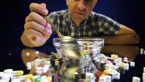 Een persoonszitting voor een kom met pillen gaat als een maaltijd eten stock footage
