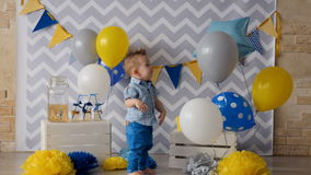 Een peuter lacht en slaat bij verbonden ballons stock footage