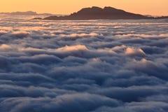 Een piek wordt omringd door overzees van wolken Royalty-vrije Stock Foto's