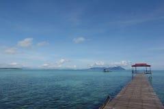 Een pier die blauwe oceaan onder ogen zien Stock Foto