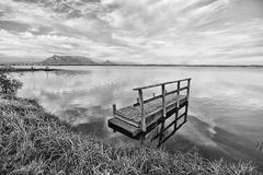 Een pier onder bewolkte hemel met berg Royalty-vrije Stock Foto's