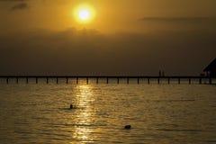 Een pijler over het overzees met silhouetten bij zonsondergang Royalty-vrije Stock Afbeelding