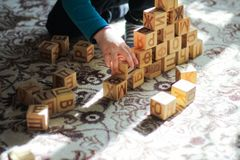 Een piramide van houten blokken en het concept een tijd-KLEINE jongen die van kinderen op de vloer spelen stock foto