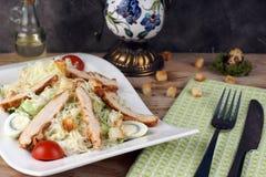 Een plaat met Caesar-salade met kip naast een groen handdoek en een bestek royalty-vrije stock afbeeldingen