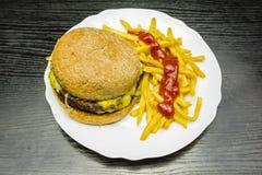 Een plaat met een hamburger, frieten en ketchup royalty-vrije stock foto
