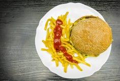 Een plaat met een hamburger, frieten en ketchup Mening van hierboven stock foto's