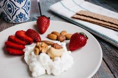 Een plaat met kwark, aardbeien en noten, een kop van koffie en handdoeken op een houten lijst royalty-vrije stock fotografie
