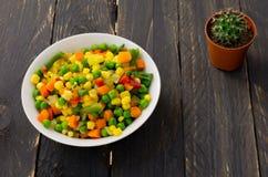 Een plaat met Mexicaanse salade en een cactus op een zwarte achtergrond Een kleurrijke salade royalty-vrije stock fotografie