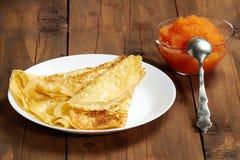 Een plaat met pannekoeken en een kom met kaviaar op de lijst Stock Afbeelding
