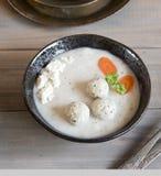 Een plaat met witte Poolse soep Witte borsjt met ei, vleesballetjes, kwark en wortelen royalty-vrije stock foto