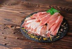 Een plaat van dun gesneden prosciutto, een Italiaanse droog-genezen ham met verse groene bladeren van munt op een houten achtergr royalty-vrije stock fotografie