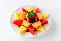 Een plaat van geassorteerd die fruit in een ster met inbegrip van watermeloen, ananas, kantaloep, druiven, braambessen, aardbeien stock afbeeldingen