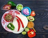 Een plaat van heerlijke taco's en voedselingrediënten Mexicaans het koken recept stock fotografie