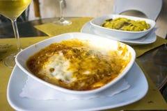 Een plaat van lasagna's met een glas witte wijn Stock Foto's