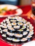 Een plaathoogtepunt van de eigengemaakte sushi van de zalmavocado rolt stock foto
