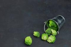Een placer van groene broccolikolen van een kleine emmer Malplaatje van gezond voedsel op een donkere achtergrond Exemplaar ruimt stock afbeeldingen