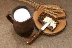 Een plak van beboterd brood op een houten raad, een slijpstof melk en rijpe oren royalty-vrije stock afbeeldingen