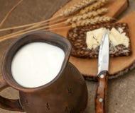 Een plak van beboterd brood op een houten raad, een slijpstof melk en rijpe oren royalty-vrije stock fotografie