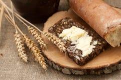 Een plak van beboterd brood op een houten raad, een slijpstof melk en rijpe oren royalty-vrije stock foto