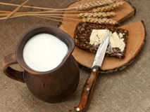 Een plak van beboterd brood op een houten raad, een slijpstof melk en rijpe oren stock fotografie