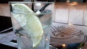 Een plak van sinaasappel in een glas met sodawater Een glas water met een plak van citroen, stock video
