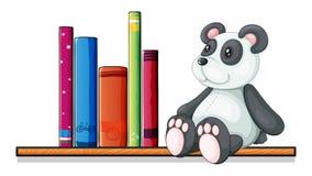 Een plank met boeken en een stuk speelgoed panda Stock Afbeeldingen