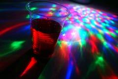 Een plastic glas op de lijst, kleurenmuziek stock foto's