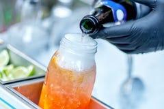 Een plastic glas van cocktail op ijs De barman giet een glas van royalty-vrije stock foto