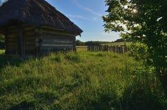 Een plattelandshuisje van stevige houten logboeken met een strodak stock afbeelding