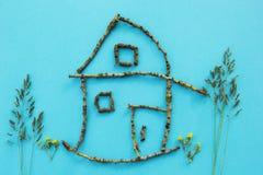 Een plattelandshuisje van stokken op een blauwe achtergrond met bomen en bloemen, concept stock fotografie