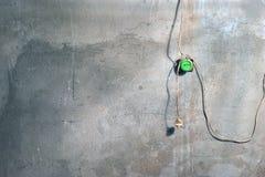 Een Pleistermuur met Barsten en Verfvlekken in de Workshop met Oude Groene Elektrische Stopcontactdoos en Hangende Draden en een  royalty-vrije stock foto's