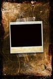 Een polaroid die aan een grungy achtergrond wordt vastgebonden Stock Foto