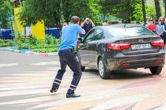Een politieagent, een wegpolitieagent in blauwe eenvormig, strijden, vertragingen, arresteert een misdadige bestuurder van een au stock foto