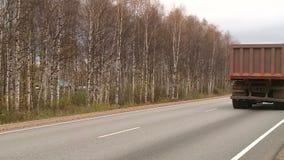 Een politiewagen drijft in de herfst langs de weg stock video