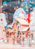 Een een pop en huis van legerkerstmis met sneeuw in de grote glasbal en het licht stock afbeelding