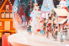 Een een pop en huis van legerkerstmis met sneeuw in de grote glasbal en het licht stock foto's