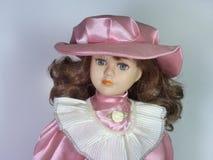 Een porseleinpop met grote mooie ogen In een elegante hoed met Stock Foto