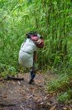 Een portier die een zware lading dragen en in het regenwoud lopen bij royalty-vrije stock fotografie