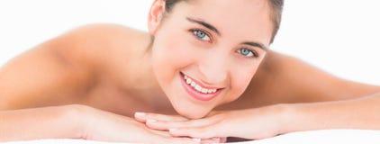 Een portret die mooi brunette op massagelijst glimlachen Stock Afbeeldingen