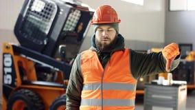 Een portret goede werktuigkundige toont tekenafkeuring, die duimen neer geven de professionele dienst van de werknemersauto toont stock videobeelden