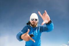 Een portret van een gebaarde reiziger op bergen die aan de muziek op de telefoon dansen en het gebaar van de camera tonen Stock Afbeeldingen