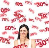Een portret van een gelukkige donkerbruine dame in een wit mouwloos onderhemd dat over kortingen droomt De rode percentagetekens  Stock Fotografie