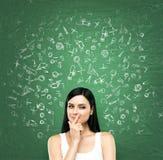 Een portret van een jonge listige donkerbruine dame die over voordelen van onderwijs denkt De dame is in een wit mouwloos onderhe Stock Afbeelding